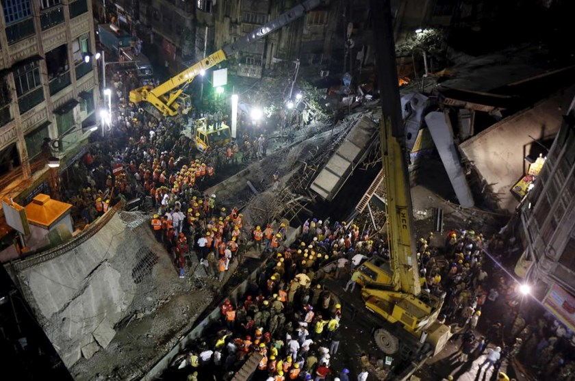 Firefighters and rescue workers search for victims at the site of an under-construction flyover after it collapsed in Kolkata, India, March 31, 2016.