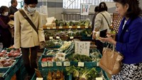 Shoppers look at vegetables at a greengrocer at Ginza shopping district in Tokyo, Japan, March 31, 2016.