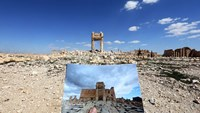 A picture of the Temple of Bel taken in 2014 is held in front of what now remains of the historic temple after the occupation of Palmyra by the Islamic State group who viewed the UNESCO-listed site's magnificent ruins as idolatrous