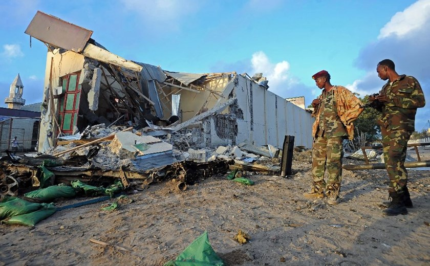 Somali soldiers and resident stand near destroyed buildings on February 27,2016 in Mogadishu, Somalia
