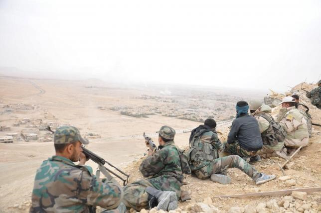 Forces loyal to Syria's President Bashar al-Assad take positions on a look-out point overlooking the historic city of Palmyra in Homs Governorate in this handout picture provided by SANA on March 27, 2016.