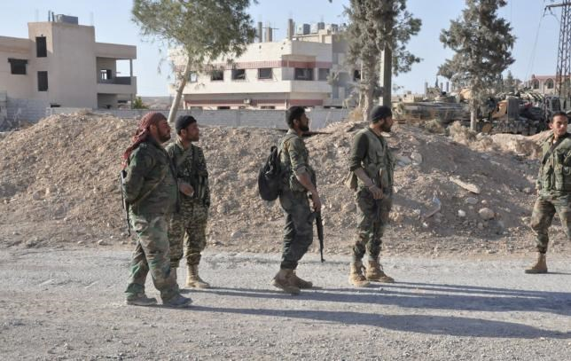Forces loyal to Syria's President Bashar al-Assad walk in the town of al-Qaryatain, Syria, after they recaptured it in this picture provided by SANA on April 3, 2016.