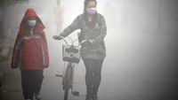 People walk along a street during a smoggy day in Jilin, Jilin province, October 22, 2013.
