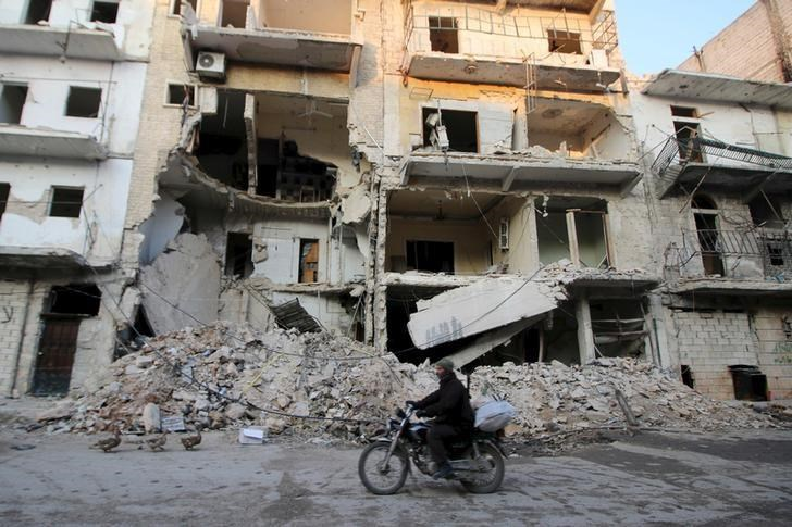 A man rides a motorcycle past damaged buildings in al-Myassar neighborhood of Aleppo, Syria January 31, 2016.