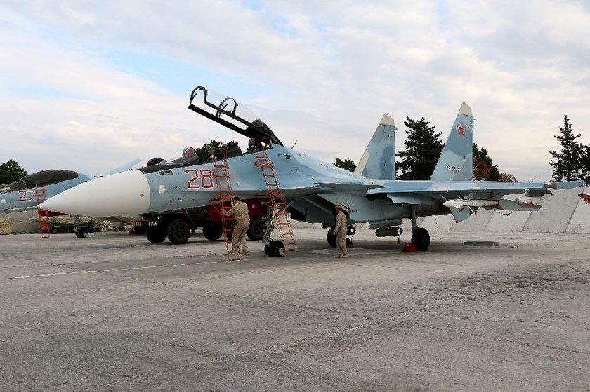 Russian servicemen prepare a Russian Sukhoi Su-30SM fighter jet at Hmeimim military base in Latakia province, Syria