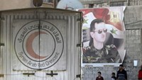 An aid convoy of the Syrian Arab Red Crescent enters the Wafideen Camp, which is controlled by Syrian government forces, near a poster of Syria's president Bashar al-Assad, to deliver aid into the rebel-held besieged Douma neighborhood of Damascus