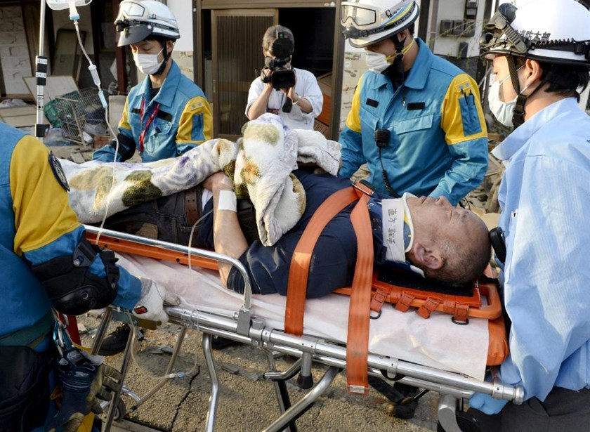 A man is carried away by a rescue workers after being rescued from his collapsed home caused by an earthquake in Mashiki town, Kumamoto prefecture, southern Japan, in this photo taken by Kyodo April 16, 2016. Photo: Reuters/Kyodo