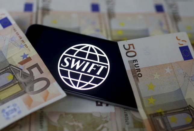 Swift code bank logo is displayed on an iPhone 6s on top of Euro banknotes in this picture illustration made in Zenica, Bosnia and Herzegovina, January 26, 2016.
