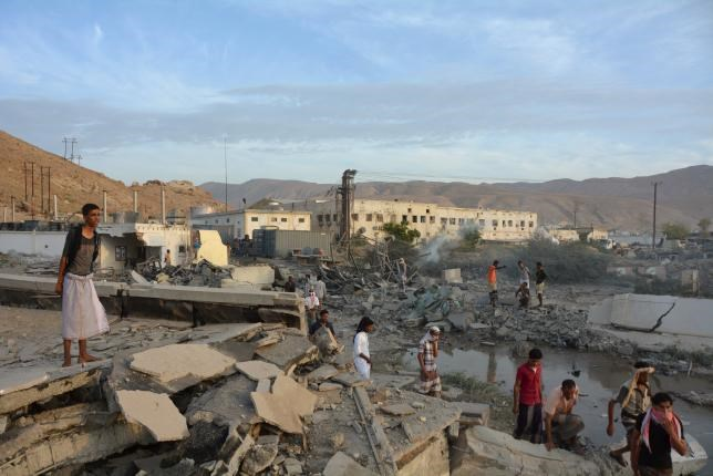People inspect damage at a site hit by Saudi-led air strikes in the al Qaeda-held port of Mukalla city in southern Yemen April 24, 2016.