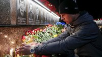 A man lights a candle at a memorial, dedicated to firefighters and workers who died after the Chernobyl nuclear disaster, during a night service in the city of Slavutych, Ukraine, April 26, 2016.