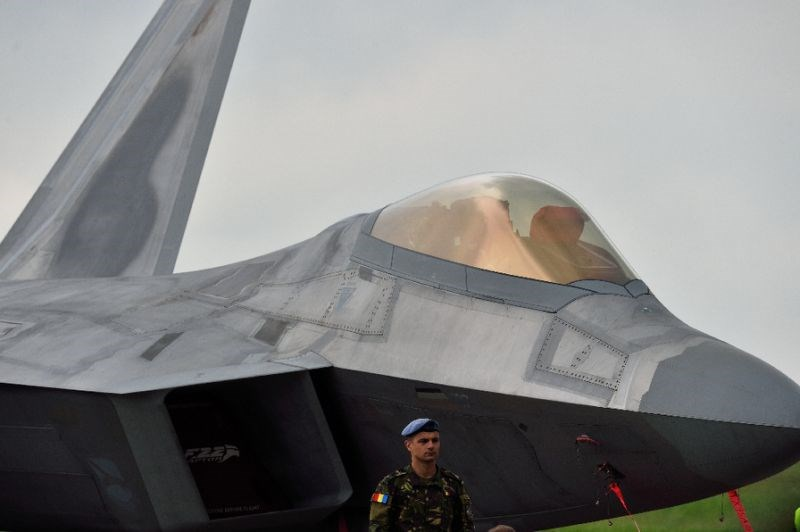A Romanian army serviceman stands next to an US fight jet F-22 Raptor at the Mihail Kogalniceanu Air Base, near Constanta, Romania, on April 25, 2016