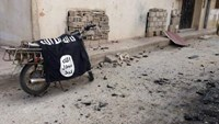 A flag belonging to the Islamic State fighters is seen on a motorbike after forces loyal to Syria's President Bashar al-Assad recaptured the historic city of Palmyra, in Homs Governorate in this handout picture provided by SANA on March 27, 2016.