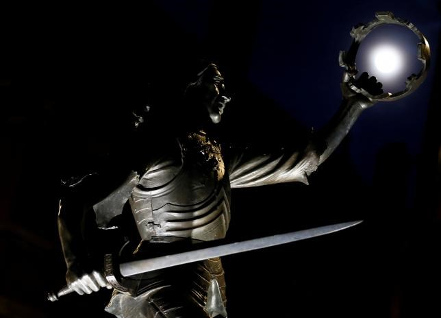 The moon is seen through the crown in the hand of the King Richard III statue in Leicester, Britain April 20, 2016.