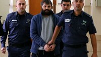 Israeli Yosef Haim Ben-David (C) the ringleader of the killing of Palestinian teenager Mohammed Abu Khdeir in 2015, is escorted by Israeli policemen at the district court in Jerusalem on March 22, 2016, prior to hearing his psychiatric evaluation