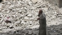 A man walks past the rubble of damaged buildings after an airstrike in the rebel held area of Aleppo's Baedeen district, Syria, May 3, 2016.