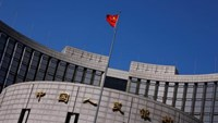 A Chinese national flag flutters outside the headquarters of the People's Bank of China, the Chinese central bank, in Beijing, April 3, 2014.