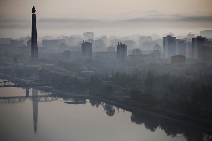 The 170-metre (558-feet) tall Juche Tower is reflected in Taedong River as morning fog blankets Pyongyang, North Korea May 5, 2016.