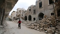 A boy rides a bicycle near damaged buildings in the rebel held area of Old Aleppo, Syria May 5, 2016.