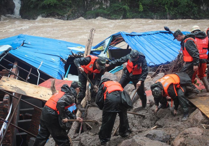 Paramilitary policemen search for missing people at the site of a landslide in Sanming, Fujian province, China, May 8, 2016. China Daily/via Reuters