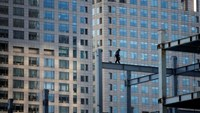 A worker walks on a beam at a construction site for a new commercial building in Beijing, December 15, 2014.