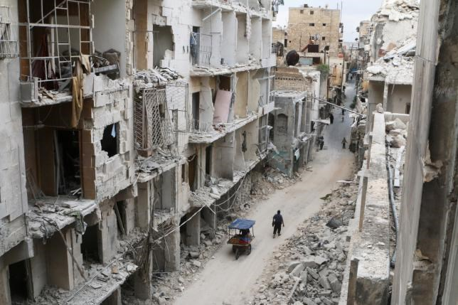Residents walk near damaged buildings in the rebel held area of Old Aleppo, Syria May 5, 2016.