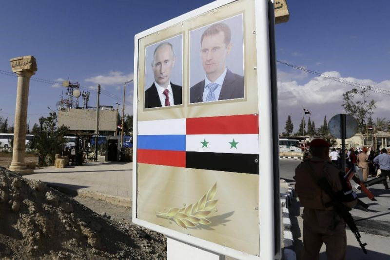 A poster in Syria's ancient city of Palmyra, captured from Islamic State militants by Russian-backed Syrian forces, bears a portrait of Syrian President Bashar al-Assad (R) and Russian President Vladimir Putin