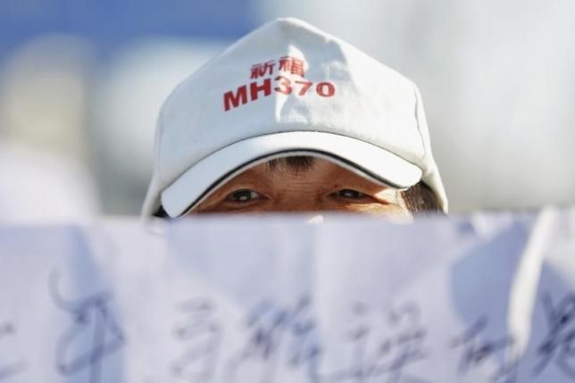 A family member of a passenger onboard Malaysia Airlines flight MH370 which went missing in 2014 holds a banner during a gathering in front of the Malaysian Embassy on the second anniversary of the disappearance of MH370, in Beijing, China, March 8, 2016.