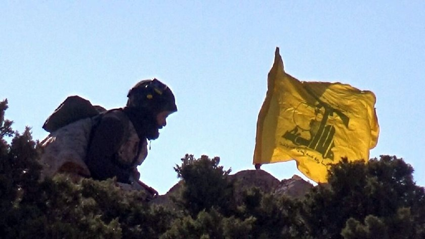 Picture released by the Hezbollah press office shows a Hezbollah fighter reportedly erecting the group's flag in the Tallet Moussa area on the Syrian side of the Qalamun hills close to the Lebanese border