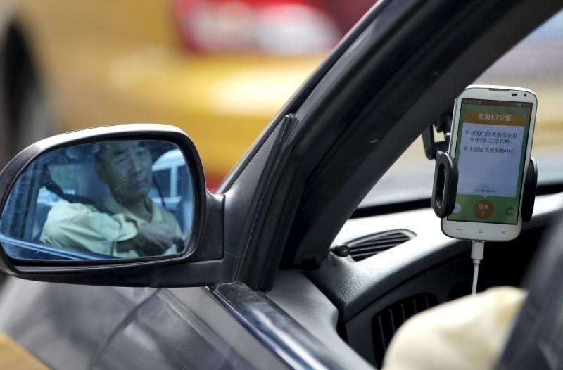 A taxi driver is reflected in a side mirror as he uses the Didi Chuxing car-hailing application in Beijing, China, September 22, 2015.