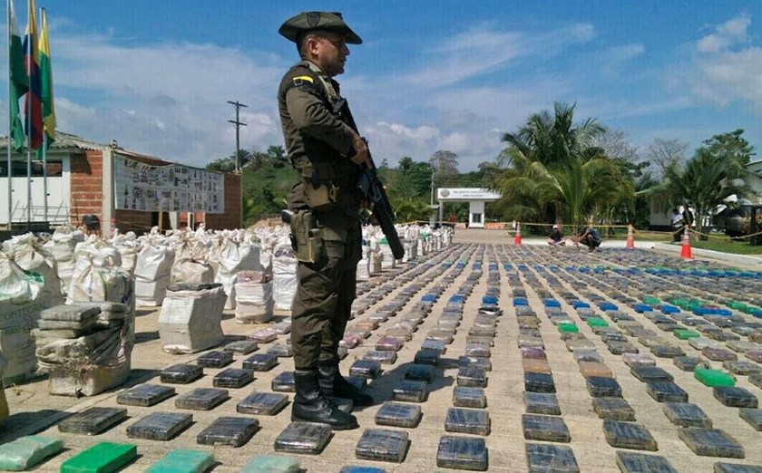 A Colombian police officer stands guard over eight tons of seized cocaine in Turbo, Antioquia department, on May 15, 2016