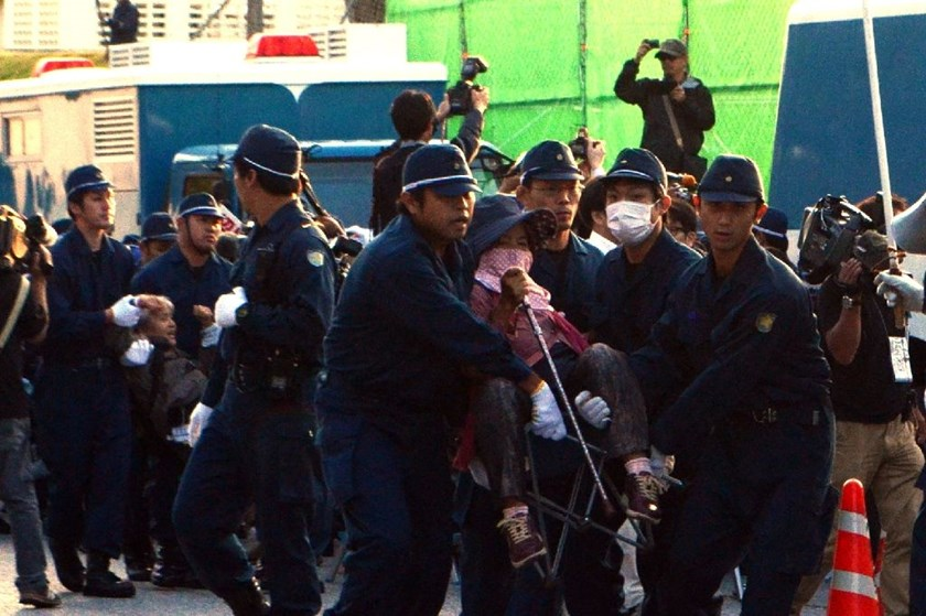 Police officers remove protesters from a gate to the US Marine base at Nago on Japan's southern island of Okinawa