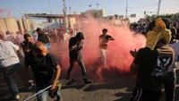 Supporters of Iraqi cleric Moqtada al-Sadr flee the smoke grenades fired by security forces after demonstrators broke into Baghdad's fortified Green Zone on May 20, 2016