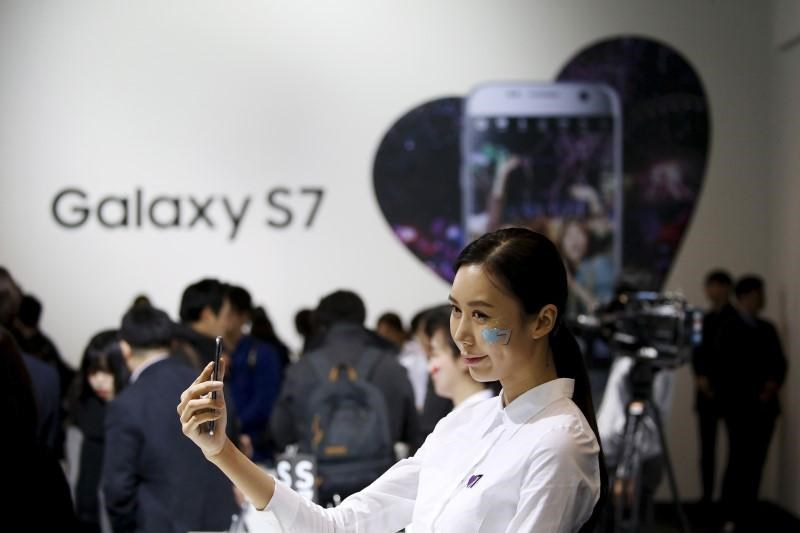 A model poses for photographs with Samsung Electronics' new smartphone Galaxy S7 during its launching ceremony in Seoul, South Korea, in this March 10, 2016 file photo.