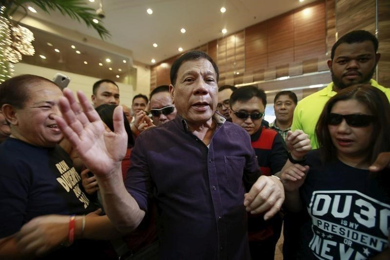 Rodrigo Duterte (C), a seven-term Philippine mayor, walks with his supporters during proclamation ceremony as a presidential candidate held at a hotel in Manila November 30, 2015