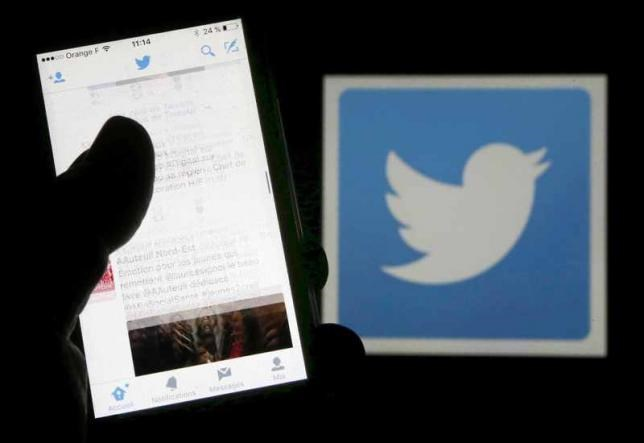A man reads tweets on his phone in front of a displayed Twitter logo in Bordeaux, southwestern France, March 10, 2016.
