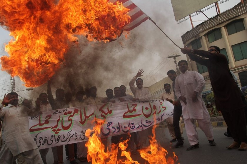 A Pakistani demonstrator holds a burning US flag during a protest in Multan on May 24, 2016, against a US drone strike in Pakistan's southwestern province Balochistan