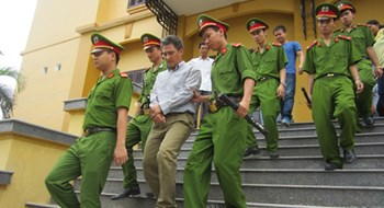 Le Van Hung is escorted out of the courthouse after his trial