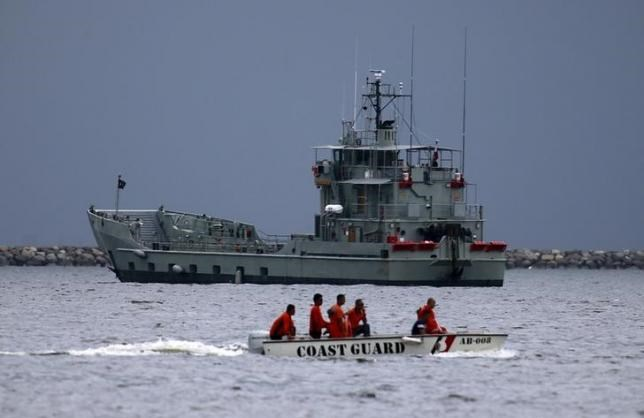 File photo of members of the Philippine coast guard on a motorboat driving past one of the two decommissioned Landing Craft Heavy (LCH) vessels donated by the Australian government to the Philippines, docked at a bay in Manila August 9, 2015.