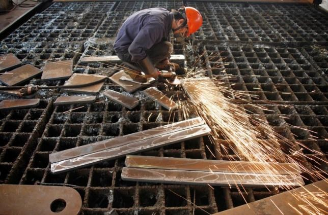 A labourer welds steel frames at a steel factory in Huaibei, Anhui province June 2, 2010.
