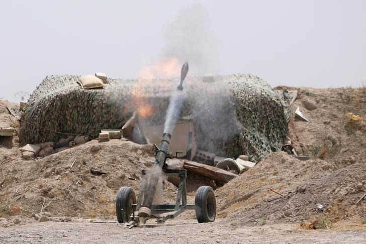 Fighters of the Syria Democratic Forces fire a mortar shell towards positions held by Islamic State fighters in northern province of Raqqa, Syria May 27, 2016.