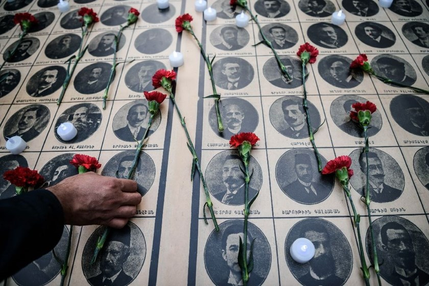 People lay flowers on images of Armenian intellectuals, detained and deported in 1915, during a rally in Istanbul on April 24, 2016 to commemorate the 101th anniversary of the mass killing of Armenians in the Ottoman Empire