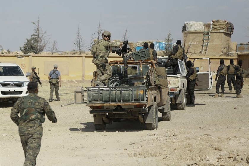Syrian Democratic forces and an armed man in uniform identified as US special operations forces (C) are seen in the village of Fatisah in the northern Syrian province of Raqa on May 25, 2016