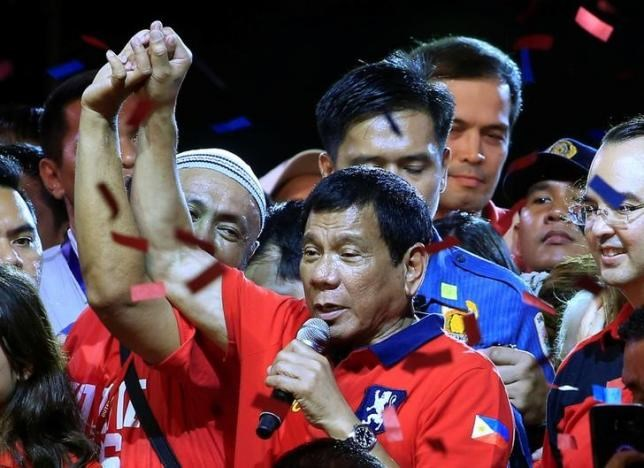 Philippine presidential candidate and Davao city mayor Rodrigo 'Digong' Duterte raised his arm by a supporter during a ''Miting de Avance'' (last political campaign rally) before the national elections at Rizal park in metro Manila, Philippines May 7, 2016.