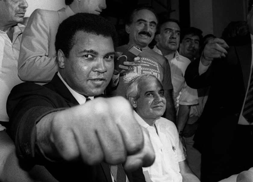 A smiling Muhammad Ali shows his fist to reporters during an impromptu press conference in Mexico City.