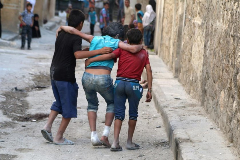 Boys help their injured friend after an airstrike on Aleppo's rebel held al-Fardous district.
