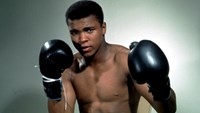 Muhammad Ali poses with his boxing gloves. Action Images/Sporting Pictures