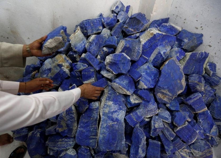 Men sort lapis lazuli inside a shop in Kabul, Afghanistan June 5, 2016.