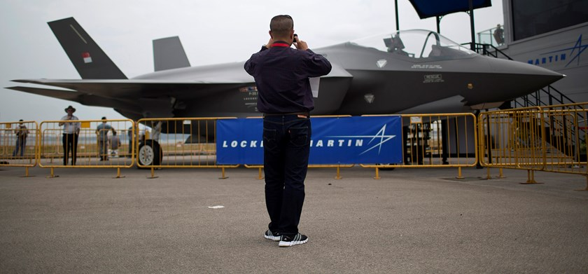 A man takes a photograph of a Lockheed Martin Corp. F-35 Lightning II fighter jet at the Singapore Airshow. Photo: Bloomberg