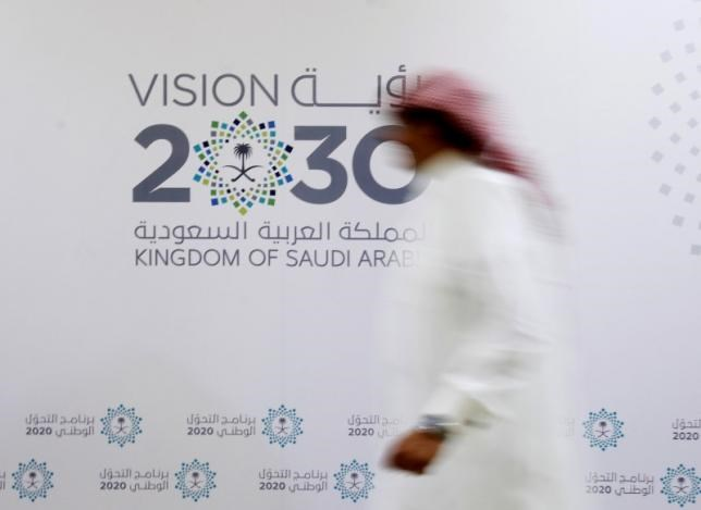 A Saudi man walks past the logo of Vision 2030 after a news conference in Jeddah, Saudi Arabia June 7, 2016.
