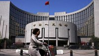 A woman rides past the headquarters of the People's Bank of China (PBOC), the central bank, in Beijing, April 3, 2014.